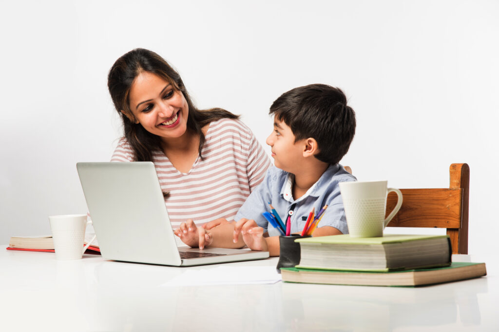 Young boy sitting with his mother in an online tutoring session