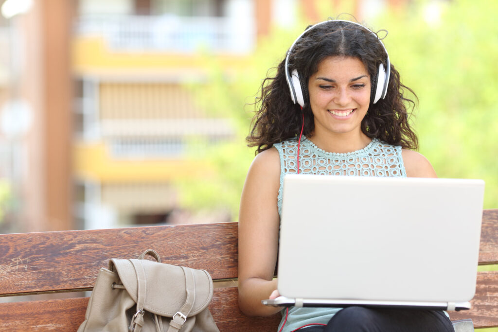 Happy girl hearing classes through online learning