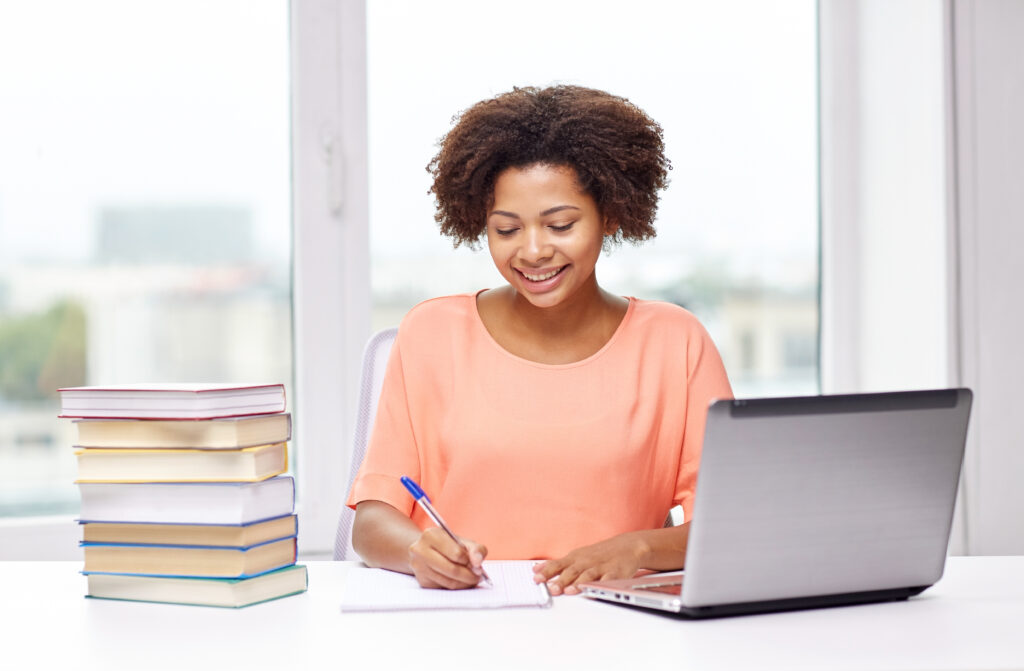 Girl taking notes in online learning